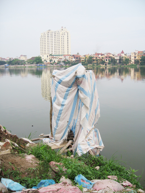 A workers' toilet on Hanoi's fashionable West Lake with the Sheraton Hotel in the background.