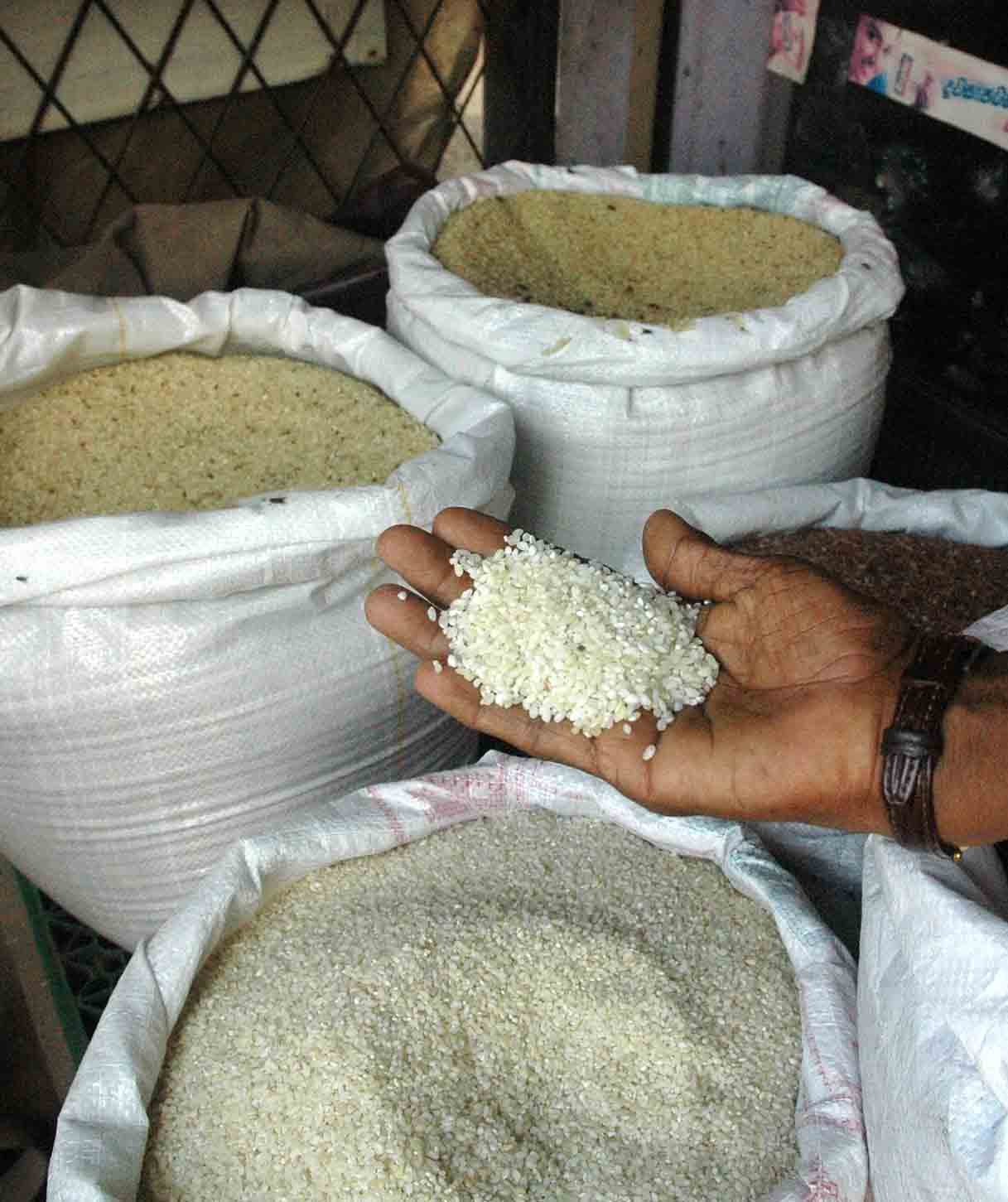 A woman checks rice at a grocery store in Colombo, Sri Lanka. With rice in short supply and at record prices, poor families are cutting back on meals and forgoing the purchase of essentials such as schooling and medical care.