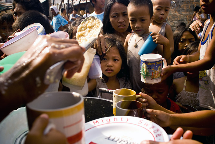 Residents of a slum in the heart of Manila enjoys free rice porridge from Non Governmental agencies during a feeding program in the area May 2008. The country faces imminent increase in rice prices that will create a domino effect amongst the prices of ba