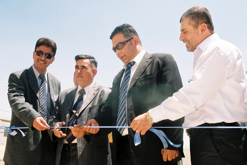 Palestinian officials in Samua cutting a ribbon to open the new reservoir.