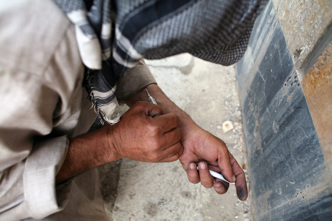 A Drug addict injects heroin in the ruins of former Soviet cultural center in Kabul Afghanistan, June 2008.