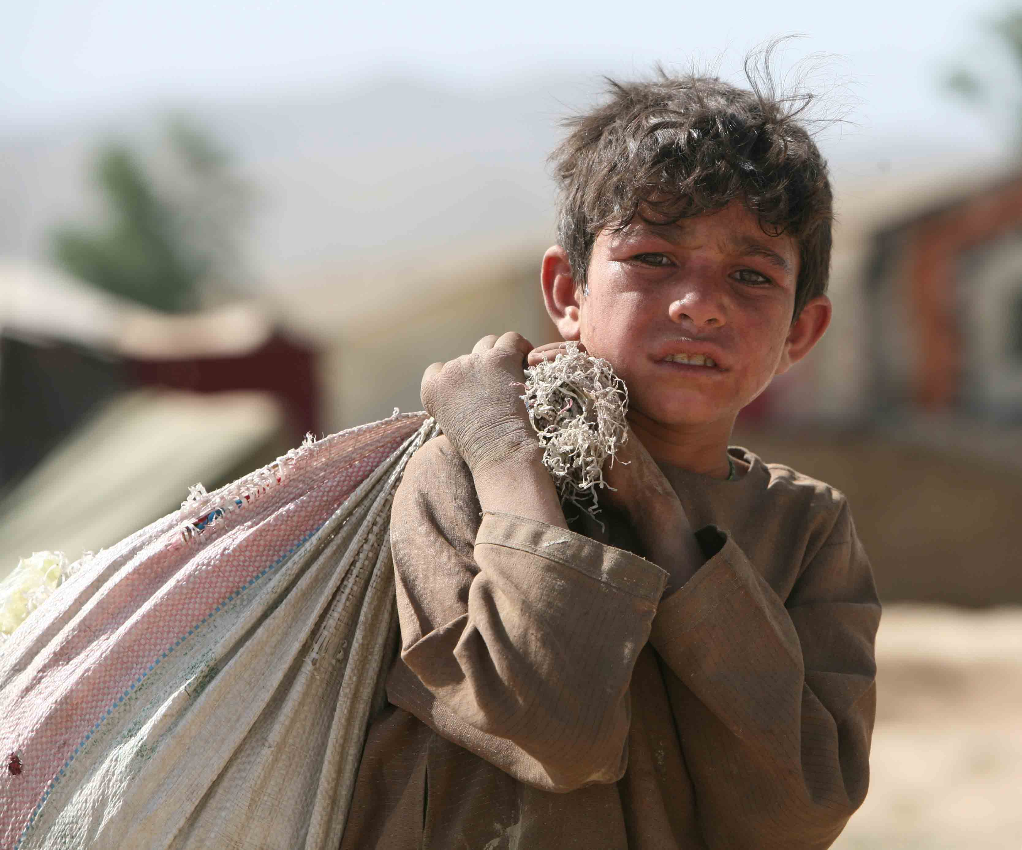 A young boy carries a heavy bag in an IDP camp in Kabul, Afghanistan June 2008. The upsurge of fighting in southern Afghanistan during 2006 has compelled tens of thousands of people to flee their homes to seek temporary refuge with relatives and friends i