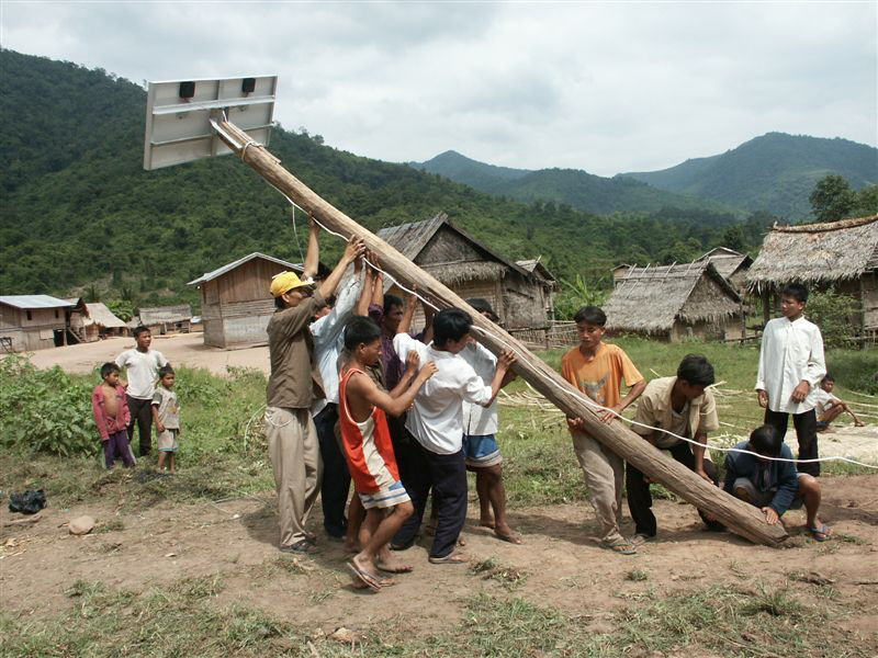 Lao villagers erect a solar panel system.
