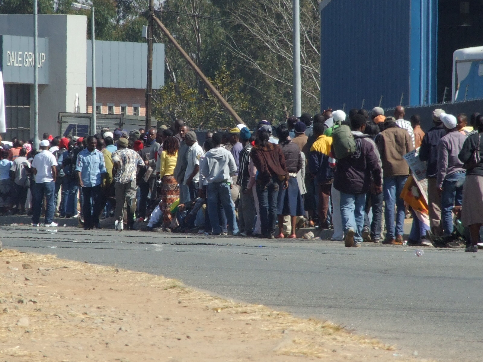 A queue of Southern Africans stretches down the street outside Crown Mines Asylum Determination Centre in Johannesburg.