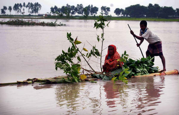 A flood-affected family moves out on a banana-raft in search of higher ground where they can await flood waters to recede. It may take days, weeks, or even months before these type of internally displaced people (IDP) can return home.