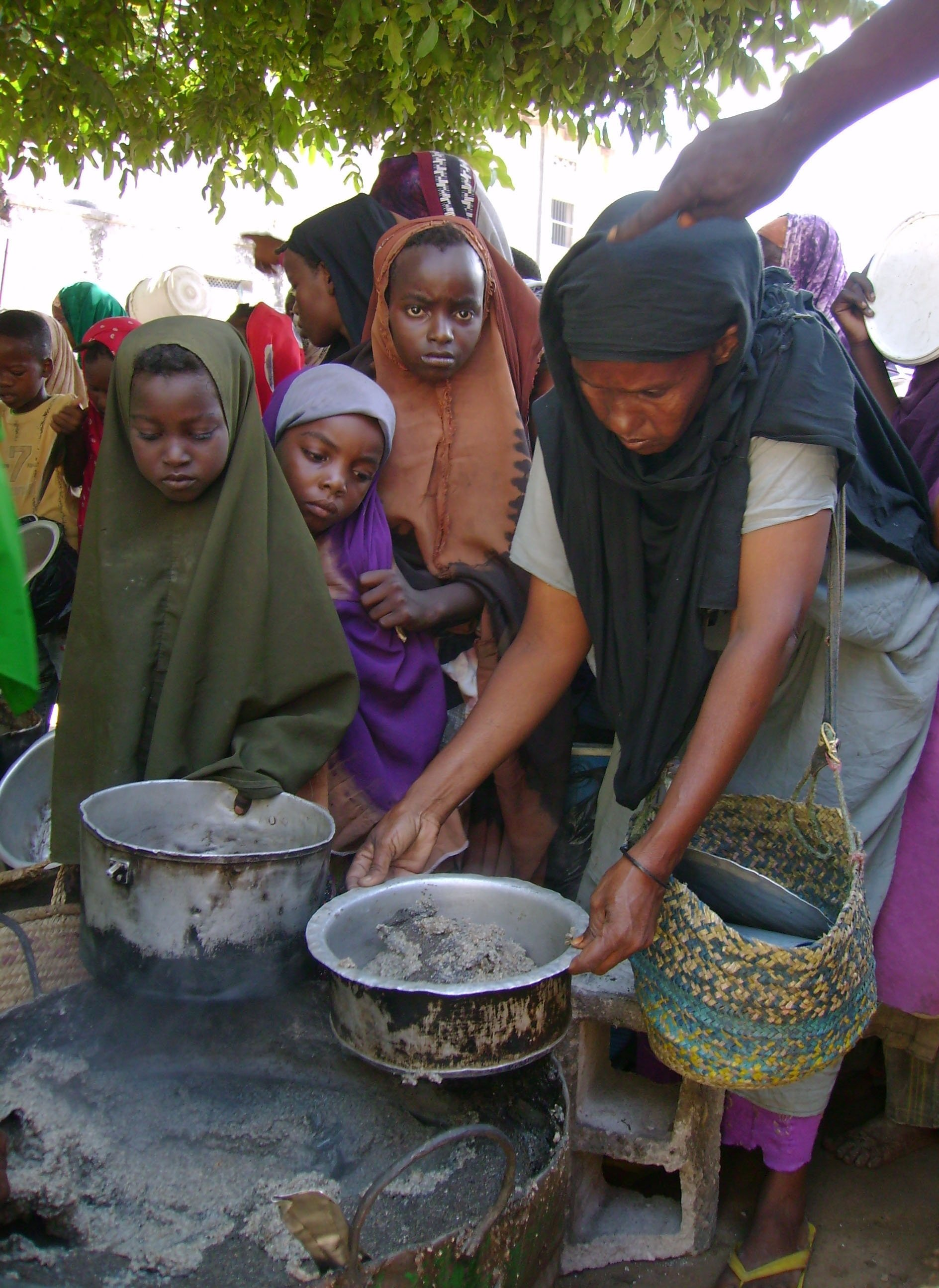 A Displaced Somali woman is given cooked food during a distribution organised by the UN World Food Programme, USAID and other local and international NGOs, in Mogadishu Somalia on September 2008.