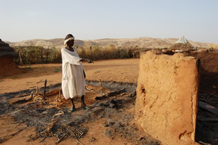 Awad Al-Karim stands amid the ruins of his home that was burnt during a recent attack on Umlaota village, near Tabit town in North Darfur.