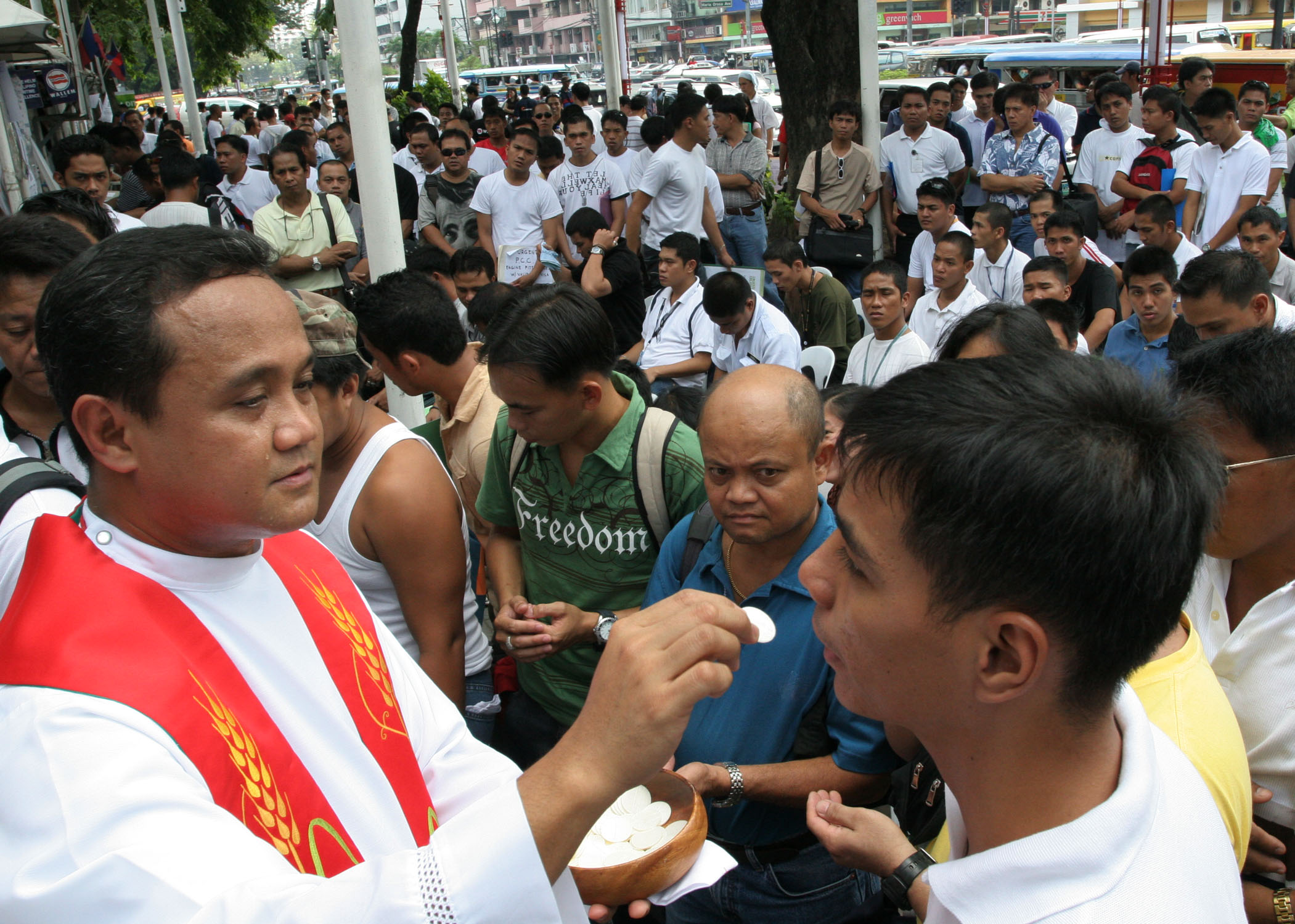 A Catholic priest gives holy communion to Filipino seafarers during a special mass at a street job fair in Manila October 18, 2008.  The Philippines is the world's fourth biggest source of migrant workers, with over eight million Filipinos employed abroad