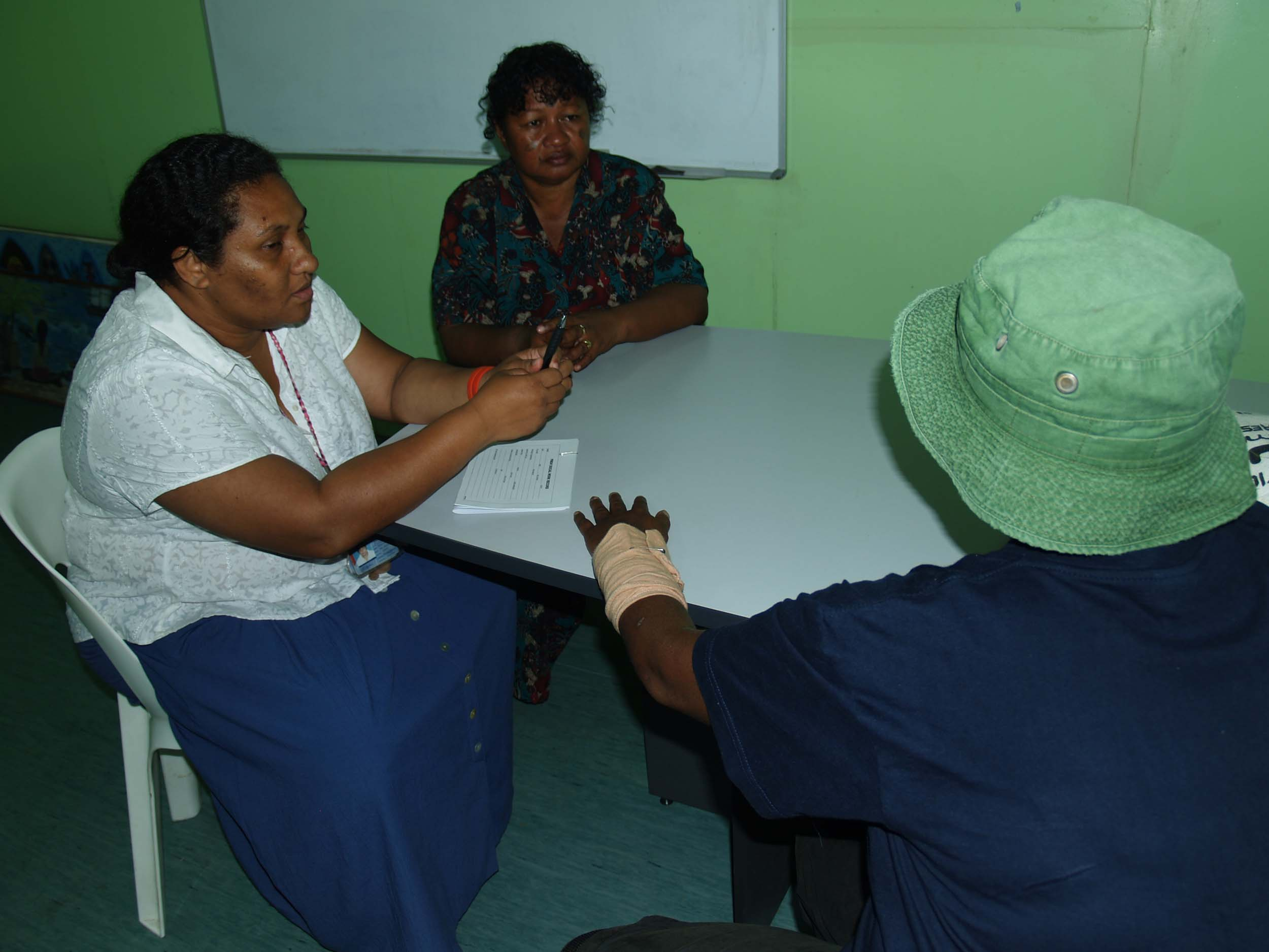 Tessie Soi, (left) who runs the Family Crisis Center at Port Moresby General Hospital and social worker Priscilla Agelava (center) counsel a woman who has been abused by her husband. Domestic violence against women and children is endemic in Papua New Gui