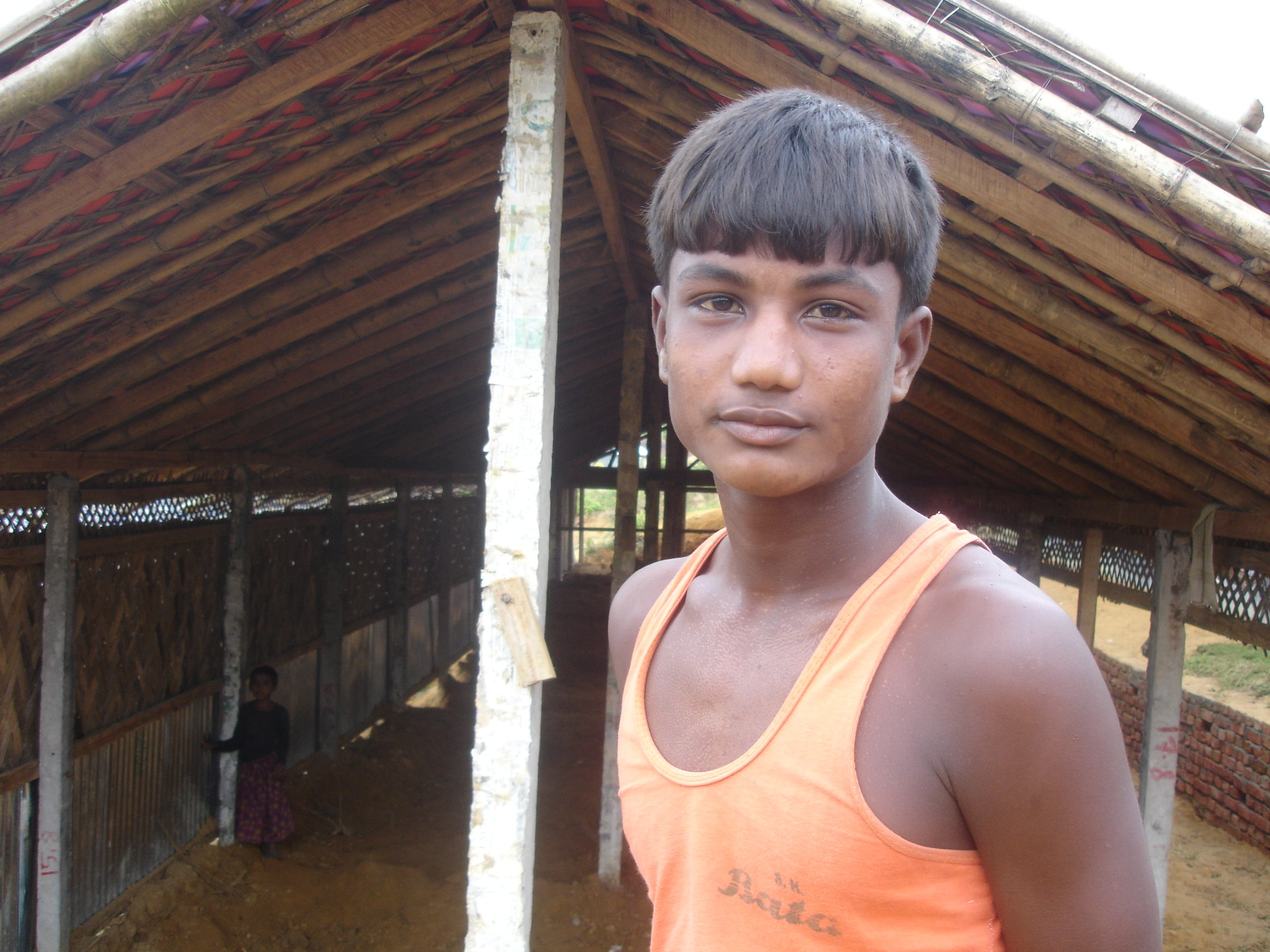 A young Rohingya man at the Kutupalong stands before one of a number of shelters now being replaced at the government-run camp.