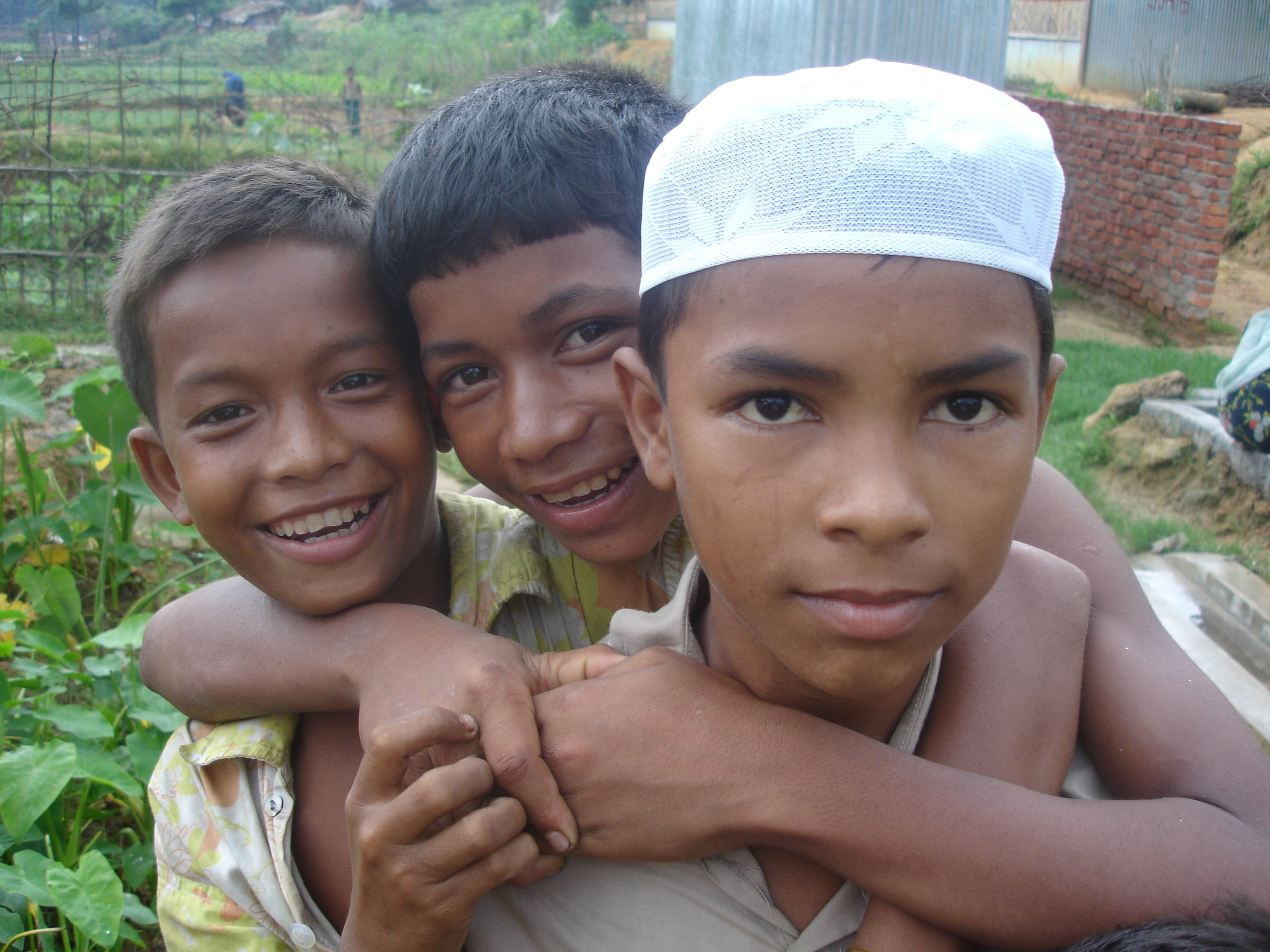 Three Rohingya boys smile to the camera in southern Bangladesh. Muslim residents from Myanmar's northern Rakhine State, the Rohingya are de jure stateless in accordance to the laws of Myanmar