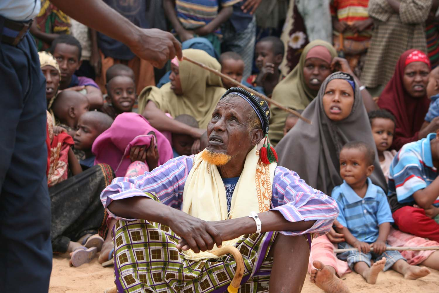 A group of newly arrived Somali refugees listens to instructions from a security officer in Dadaab, Kenya, October 2008. The conflict in Somalia has forced many people to seek refuge in northeastern Kenya.