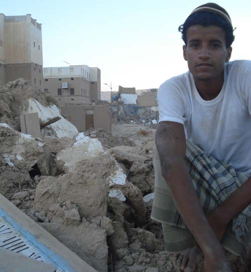 Mohammed Omar sitting on the ruins of his destroyed house.