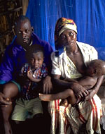 A family sits on a bed with a mosquito net behind them, in the town of Chokwe, Mozambique. Proper use of bed nets impregnated with insecticide can reduce malaria deaths by up to 50 per cent