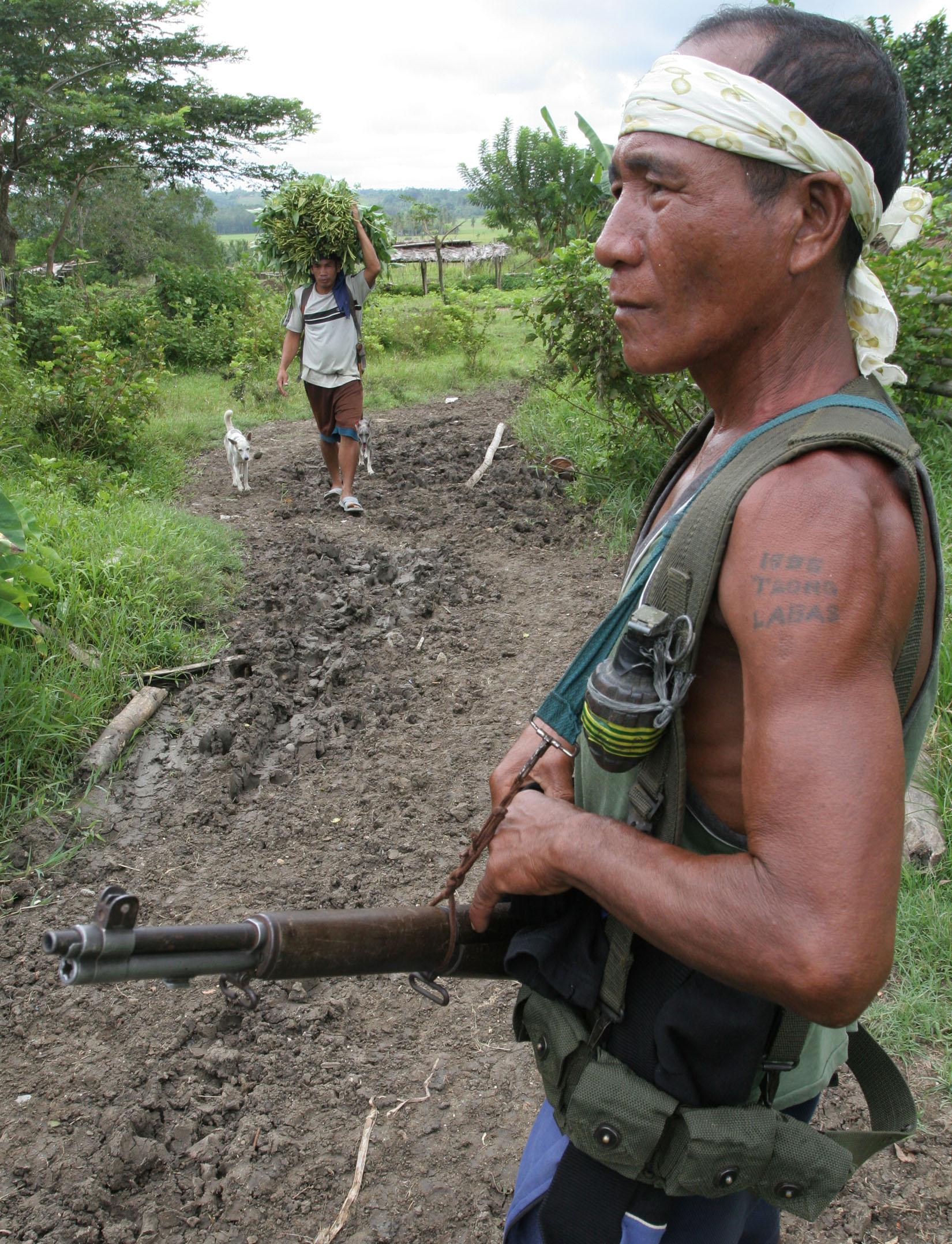 A member of a Christian militia group guards a roadside near a farming community in Mindanao. Civilians are increasingly arming themselves on the island to protect against raids by Muslim separatist rebels, in what officials warned could lead to more viol