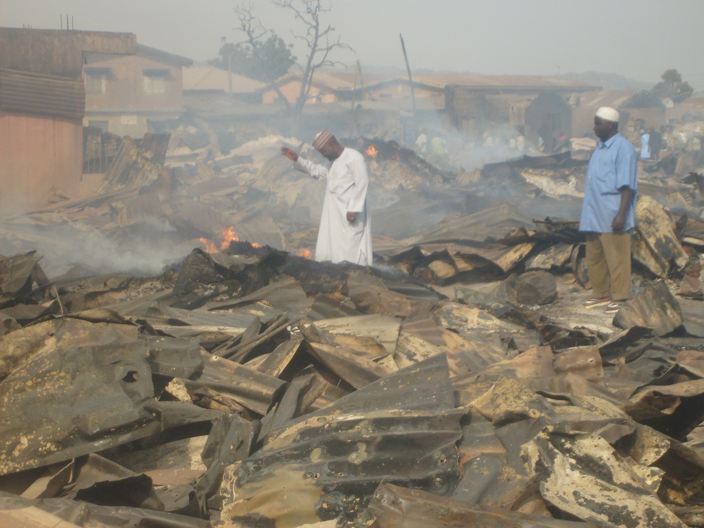 Grains traders plough through the remains of Laranto grain market before it was burned down in the Jos riots