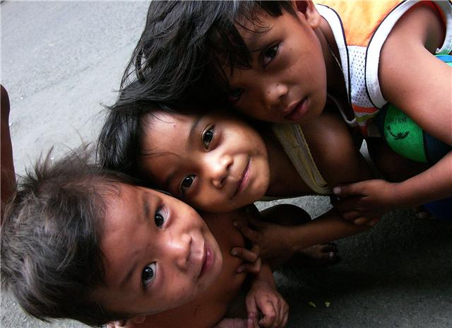 Children on a street at an overcrowded urban housing project in Manila. Experts say children are among those heavily affected by continued migration of Filipino workers abroad, with studies showing that children of migrants suffer psychological problems,