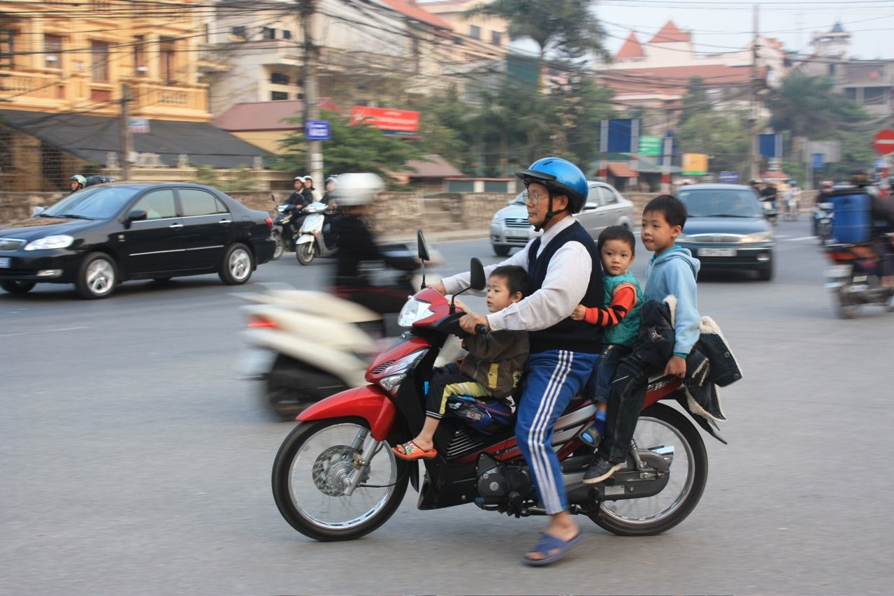 A grandfather ferries his grandchildren home. The Vietnam government established a helmet law a year ago with stiff finds for those not wearing them. Ironically, the fines do not apply to children under 16 so many go helmetless