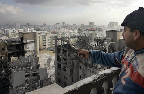 A Palestinian man looks out towards destroyed Hamas government buildings following an Israeli air strike in Gaza City on 30 December 2008. Earlier in the day, Israeli aircraft dropped at least 16 bombs on five Hamas government buildings in a Gaza City com
