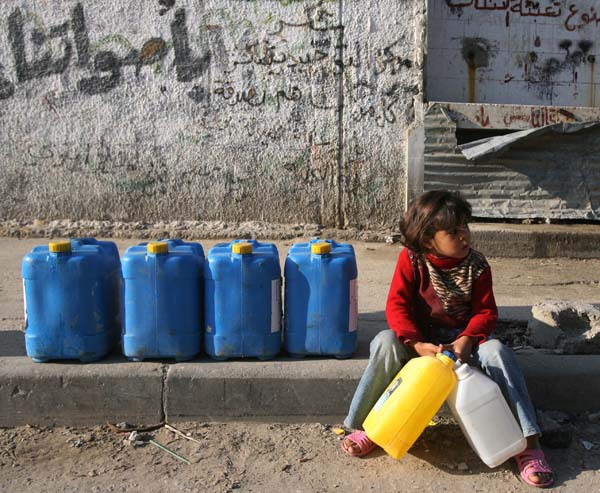 A Palestinian girl in Gaza takes a rest on her way to collect drinking water