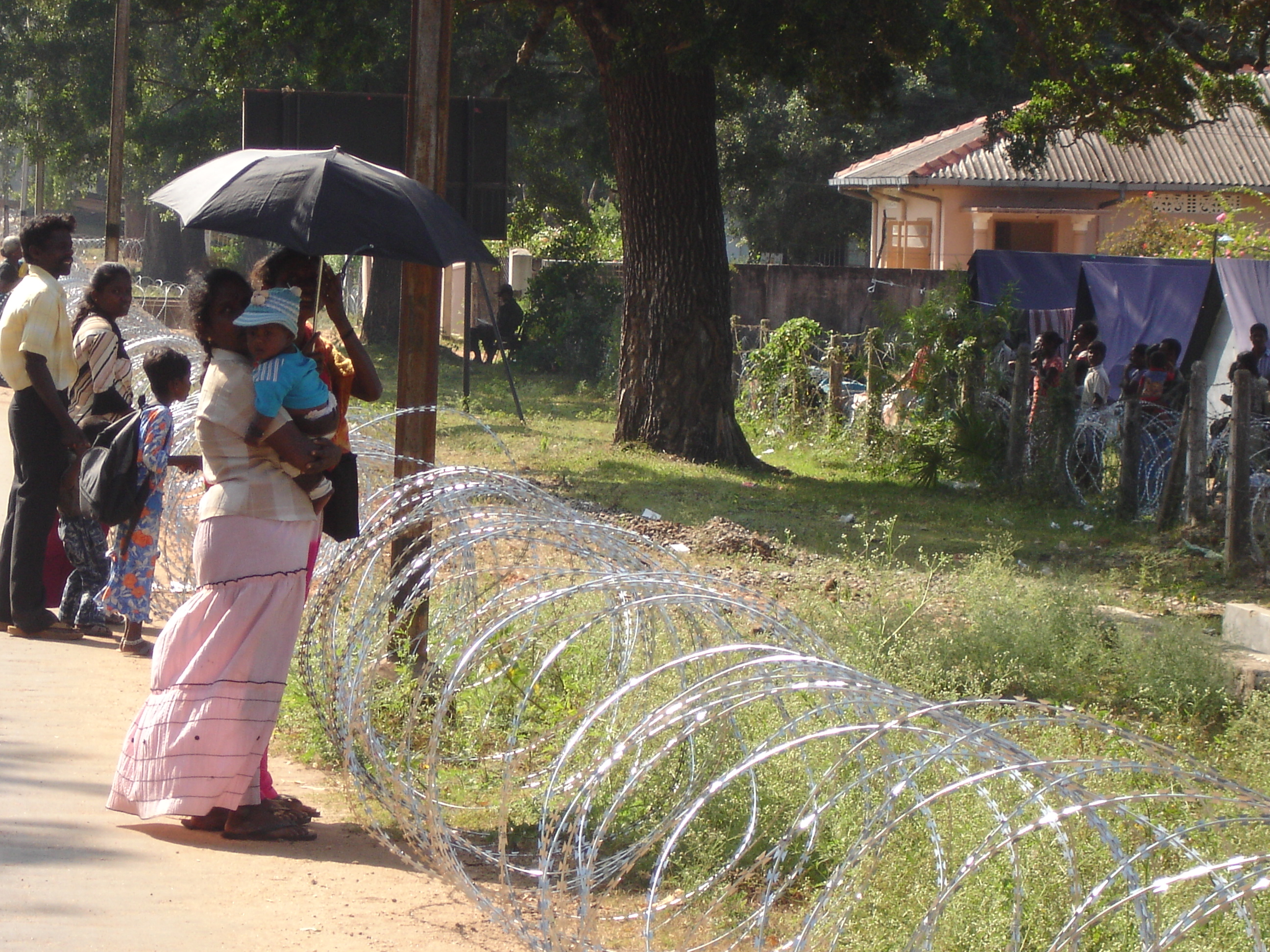 In the northern Sri Lankan town of Vanuniya, a young Tamil woman attempts to speak to family members now being interned at a displaced persons transit site through barbed wire. More than 30,000 Tamil civilians fled to government-control territory in early
