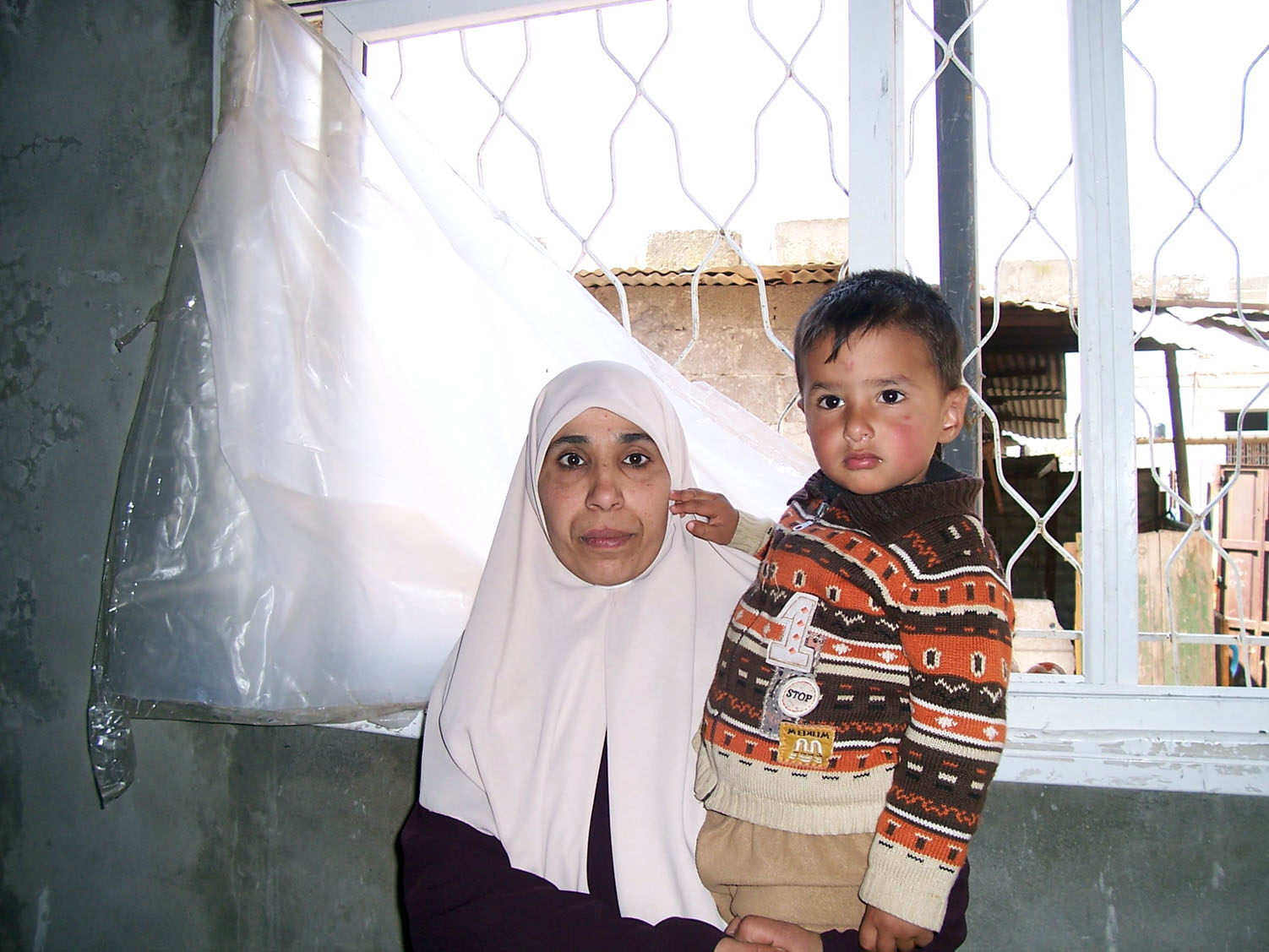 Two-year-old Ahmed from the Al-Tufa area of Gaza City lost his father during the recent conflict. His aunt and uncle are now his primary caretakers. Ahmed is seen being held by his aunt next to the missing windows of their home, shelled by Israeli tank-fi
