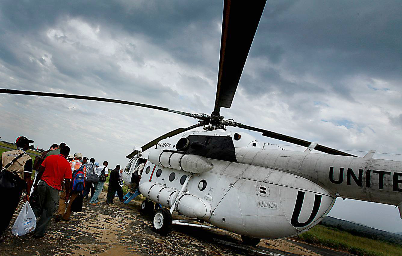 UN employees queue up to board a UN helicopter bound for Dungu at the airport in Bunia, DR Congo, on the 17th June, 2008. MONUC, the UN mission in Congo, has recently deployed peace keeping forces to Dungu to build a runway, in preparation of the arrival