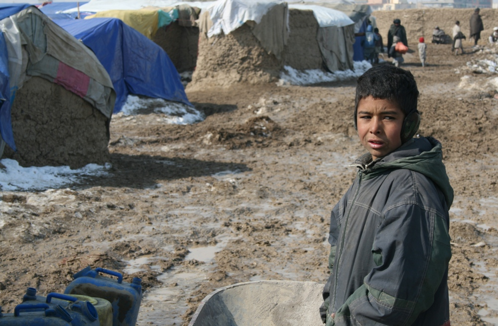An internally displaced boy stares outside a camp in Kabul