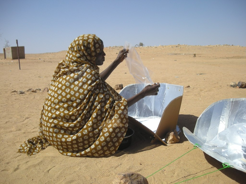Woman in a refugee camp in eastern Chad, with solar cooker. The daily needs of the local population and a quarter-million refugees are squeezing already scarce resources