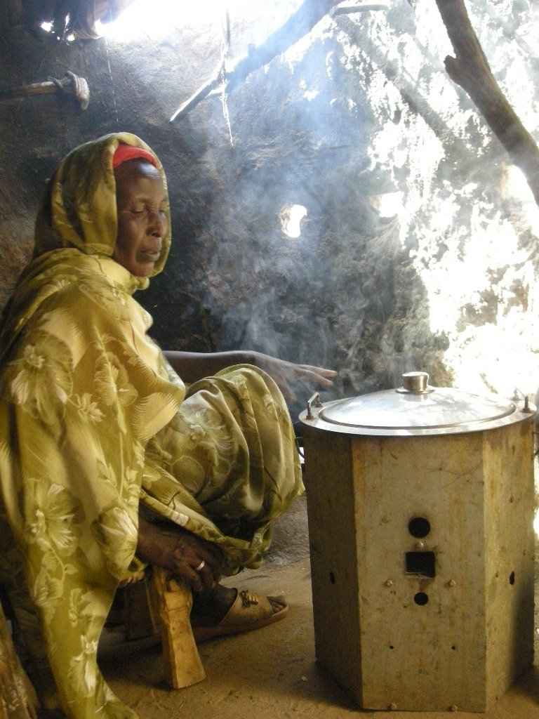 Woman in a refugee camp in eastern Chad, with an energy-efficient cooker. The daily needs of the local population and a quarter-million refugees are squeezing already scarce resources like wood and water