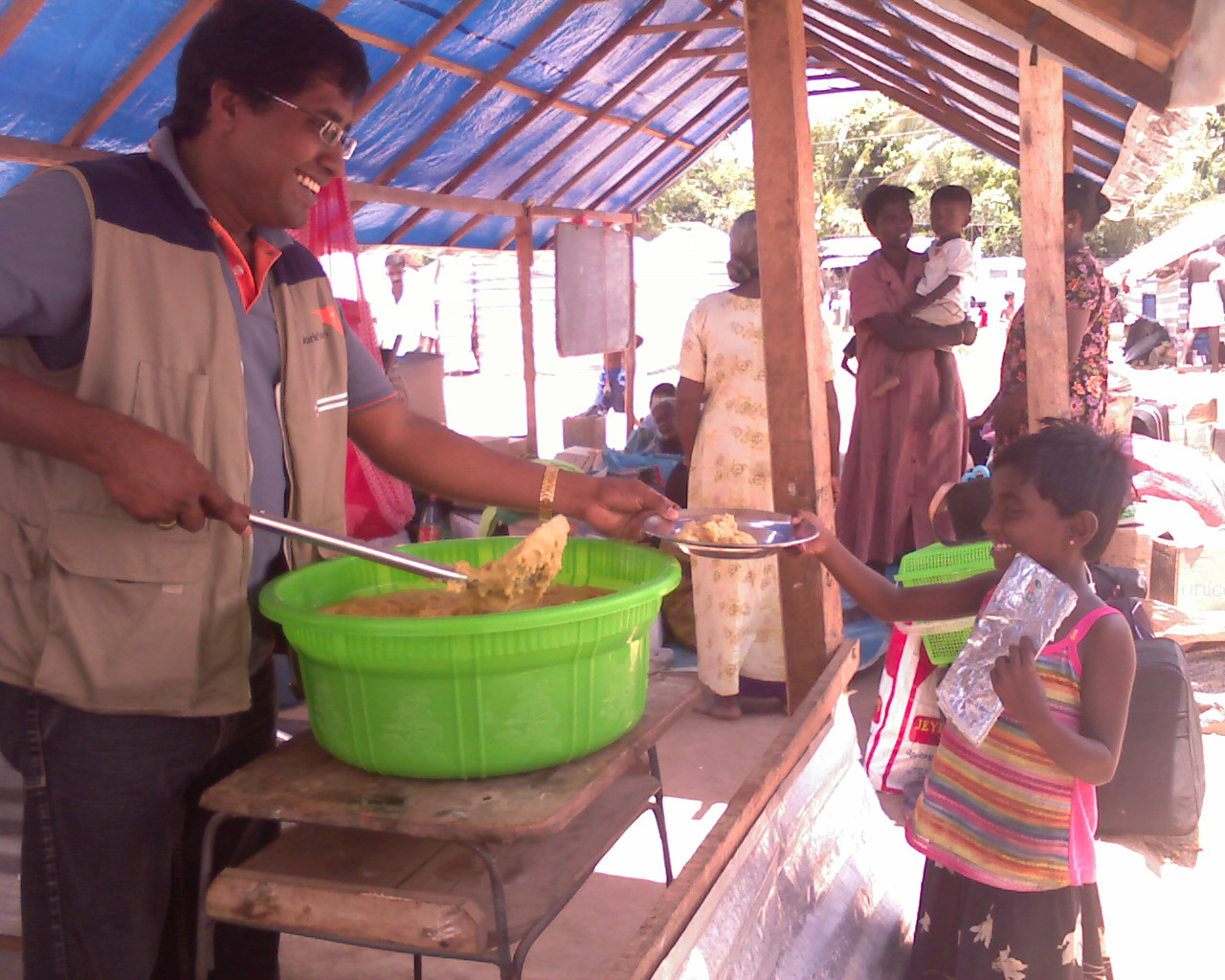 A young girl receives food assistance at an IDP camp in northern Sri Lanka. The nutritional status of thousands of children in the camps is a source of concern for aid workers on the ground