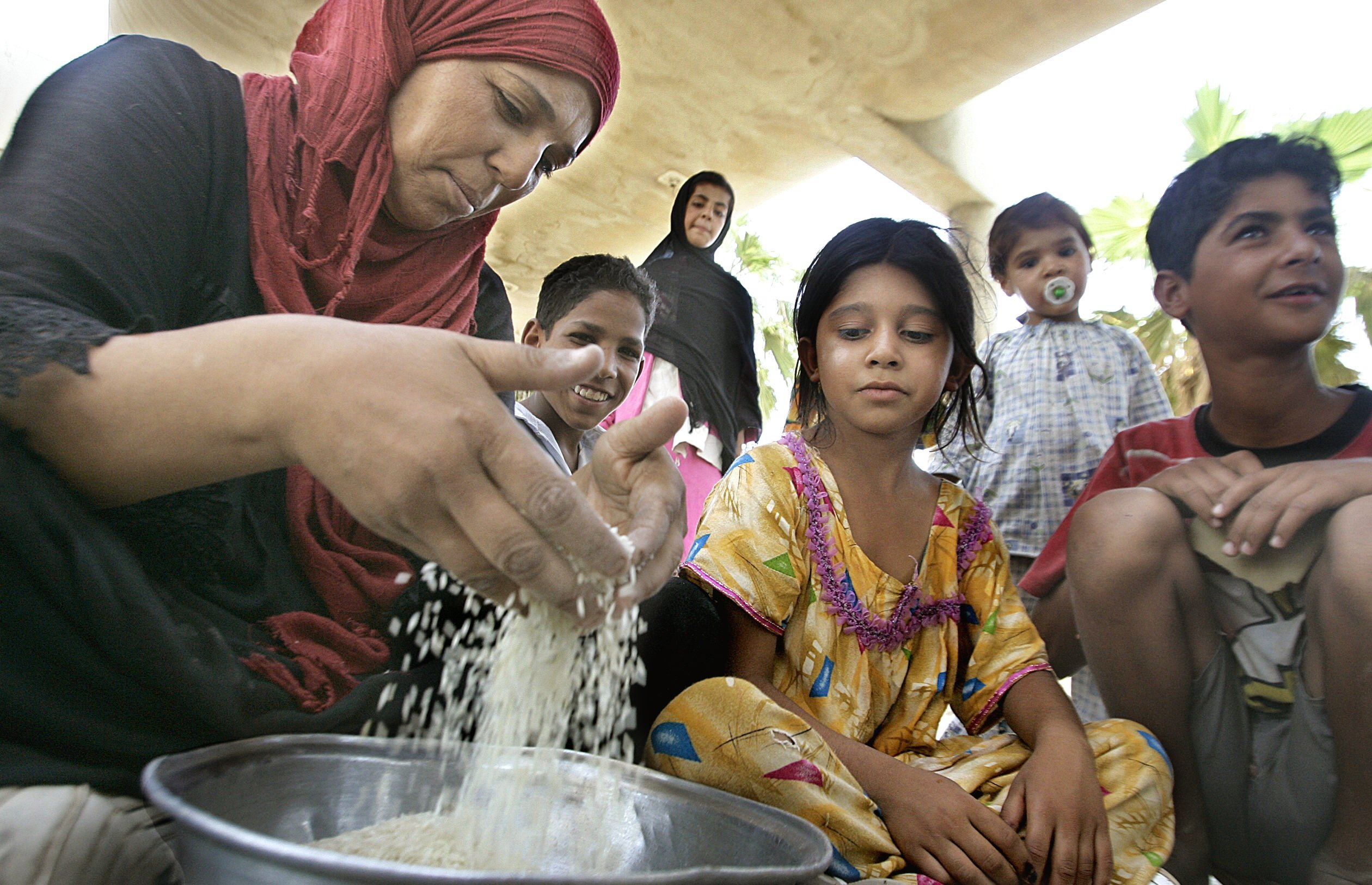A displaced women prepares food for her children at IDP camp in Baghdad in 2008