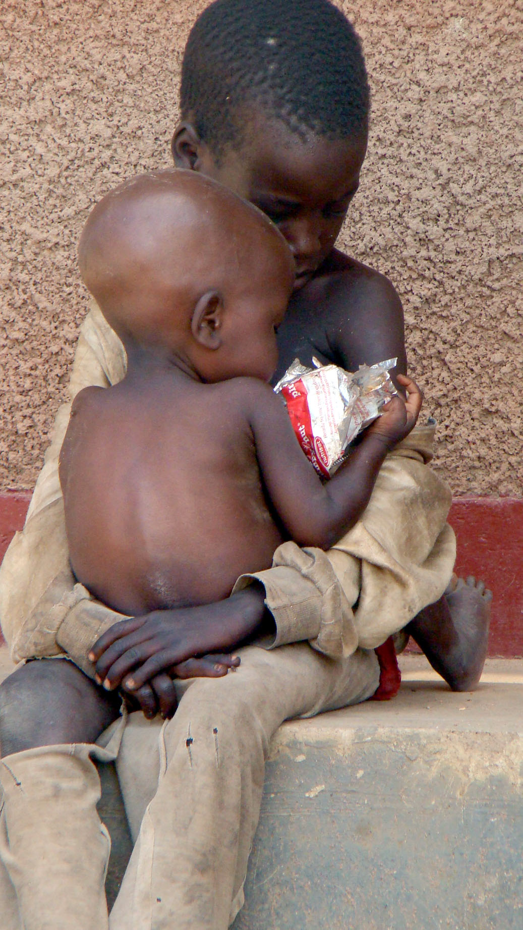 Two children in northern Uganda's Amuru district share a packet of a nut paste used as a therapeutic food