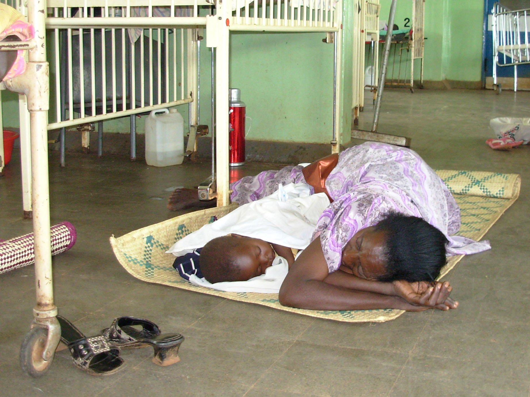 A mother lying on a bare floor at Kayunga pediatric ward on June 18, 2009. Uganda's health facilities are in a sorry state