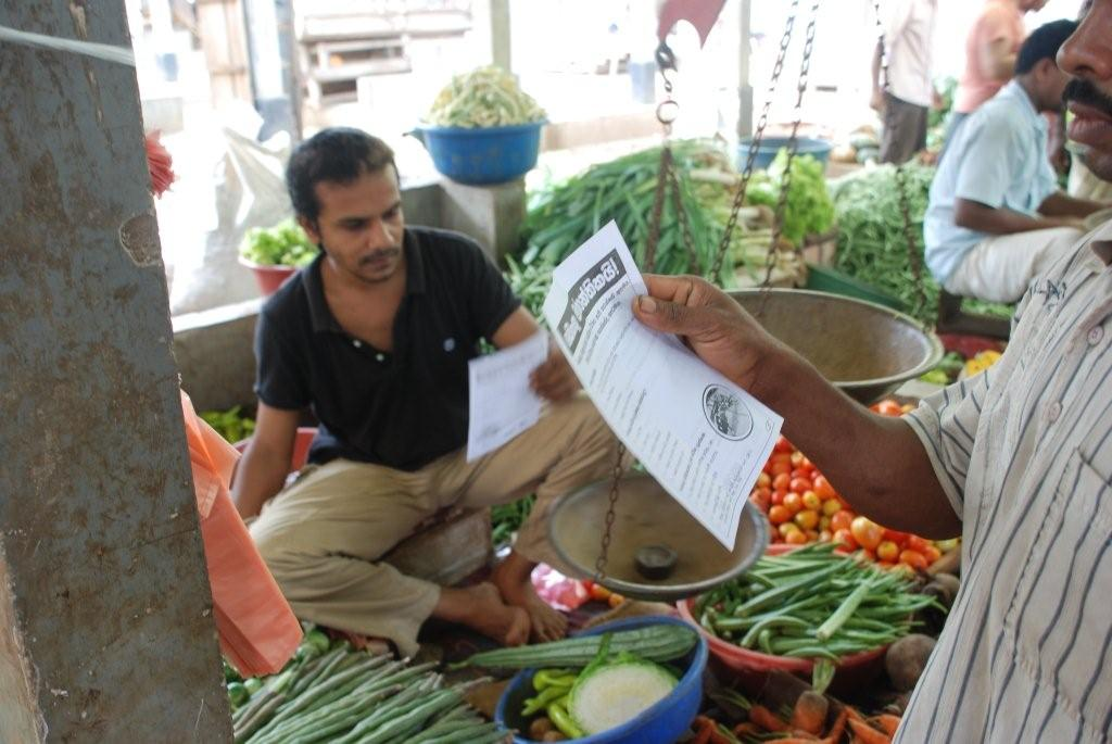 At a local market in Sri Lanka, residents read a pamphlet on the risk of dengue