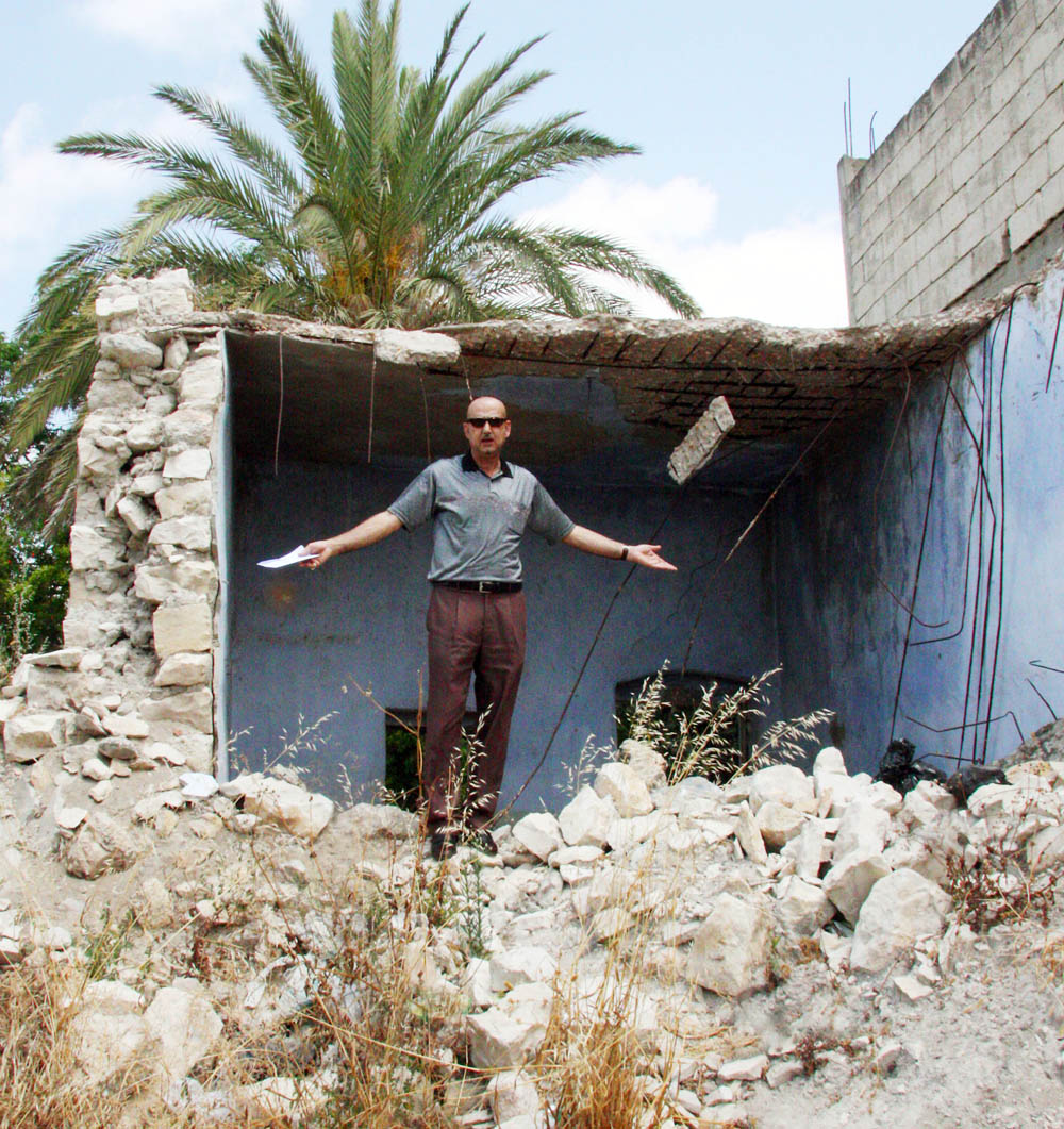 Ali Zein, Mayor of Shour village in South Lebanon, inspects earthquake damage from last year