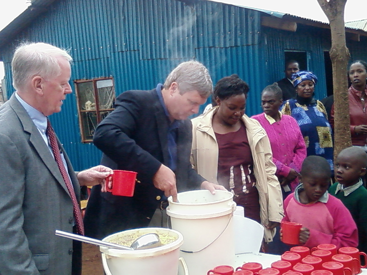 US Secretary of Agriculture Tom Vilocack and US ambassador Micheal Ranneberger feed children in Kibera