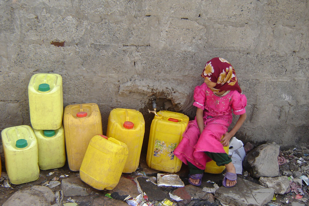 A girl attempting to fill containers with the trickling water from a tap near an artesian well outside the capital, Sanaa