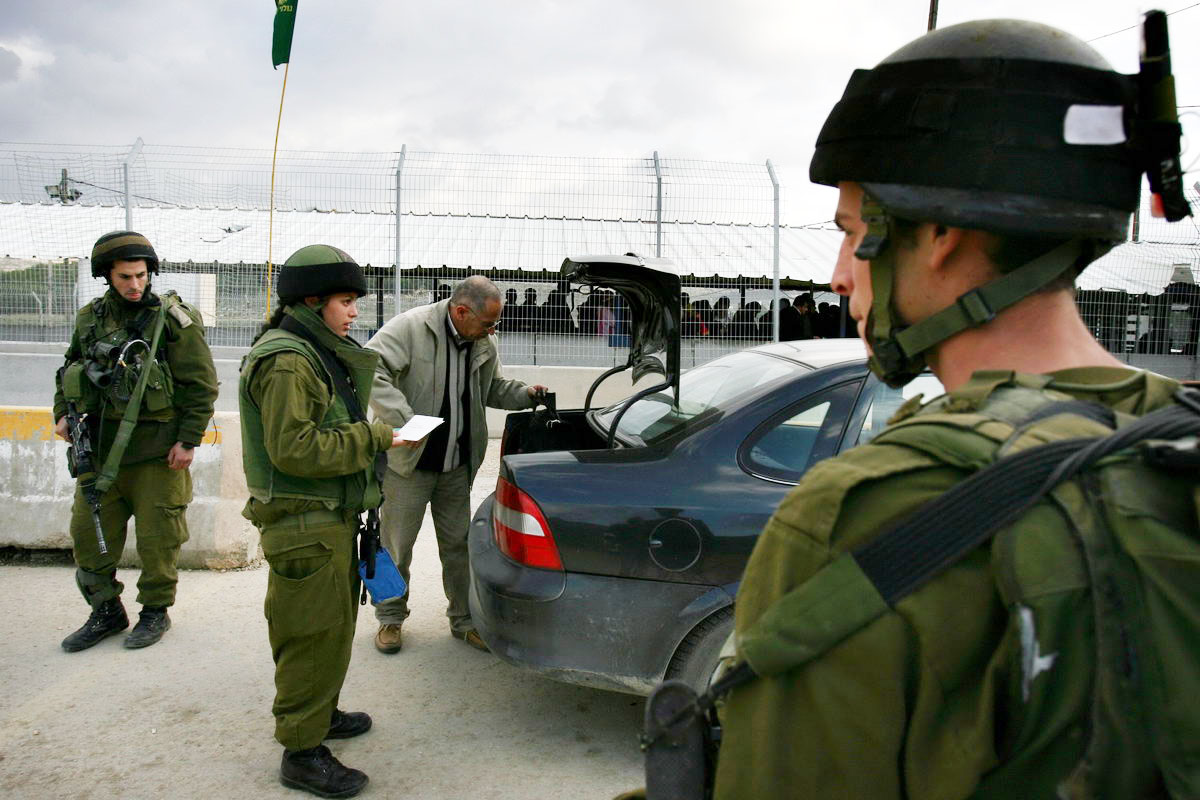 Israeli soldiers search a Palestinian's car at the Hawera checkpoint outside the town of Nablus in the West Bank