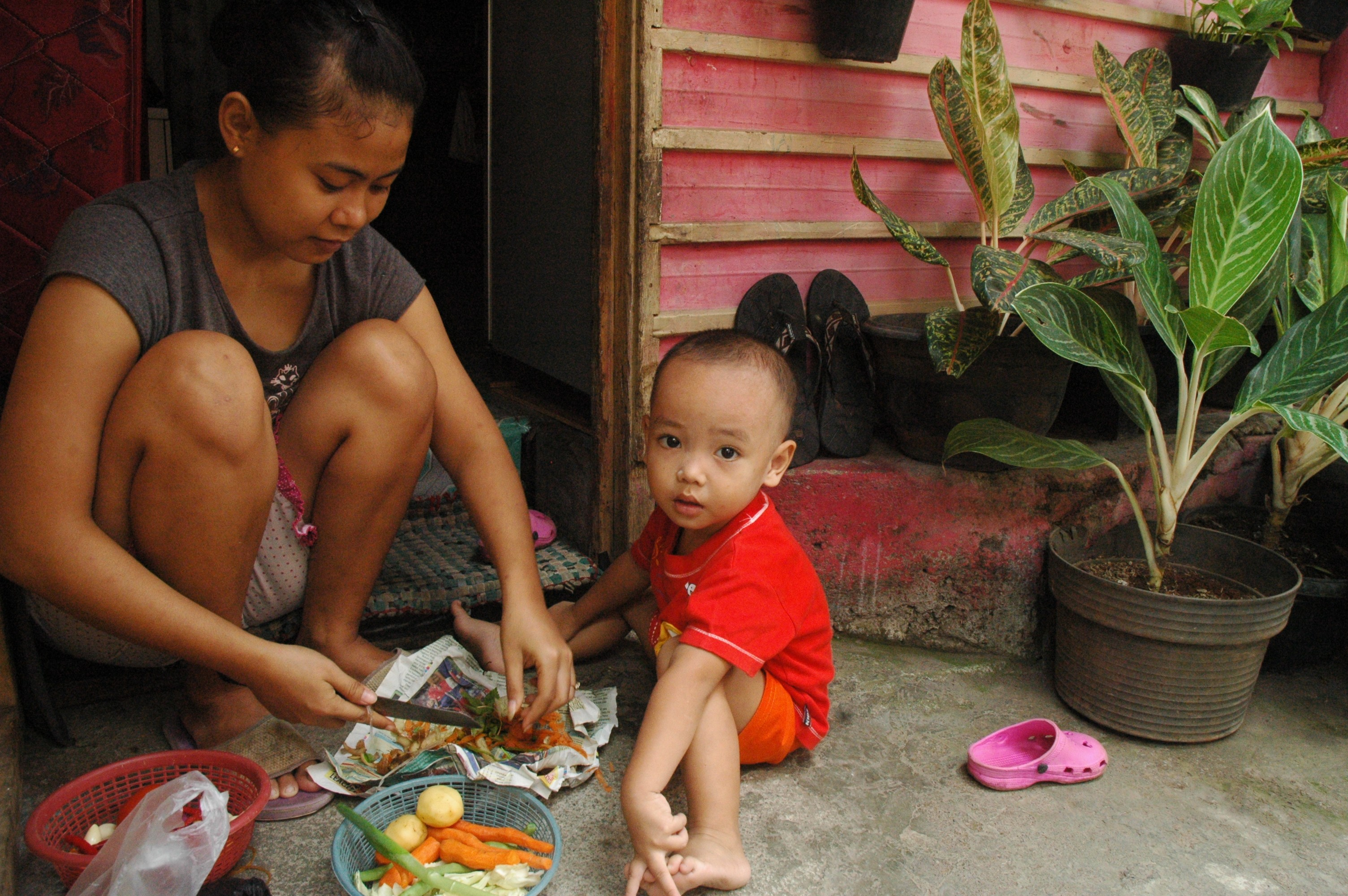A young mother and her child outside their home near Jakarta. Thousands of children are unregistered in the country.