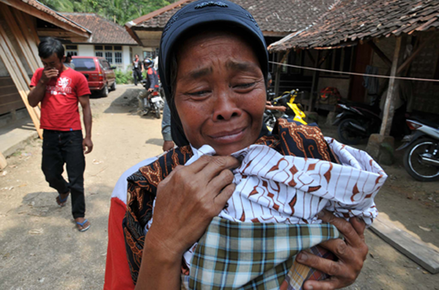 A survivor cries after an earthquake damaged her house at Pamoyanan Village, Cibinong Distric in Cianjur Regency , West Java, Indonesia, on 2 September 2009