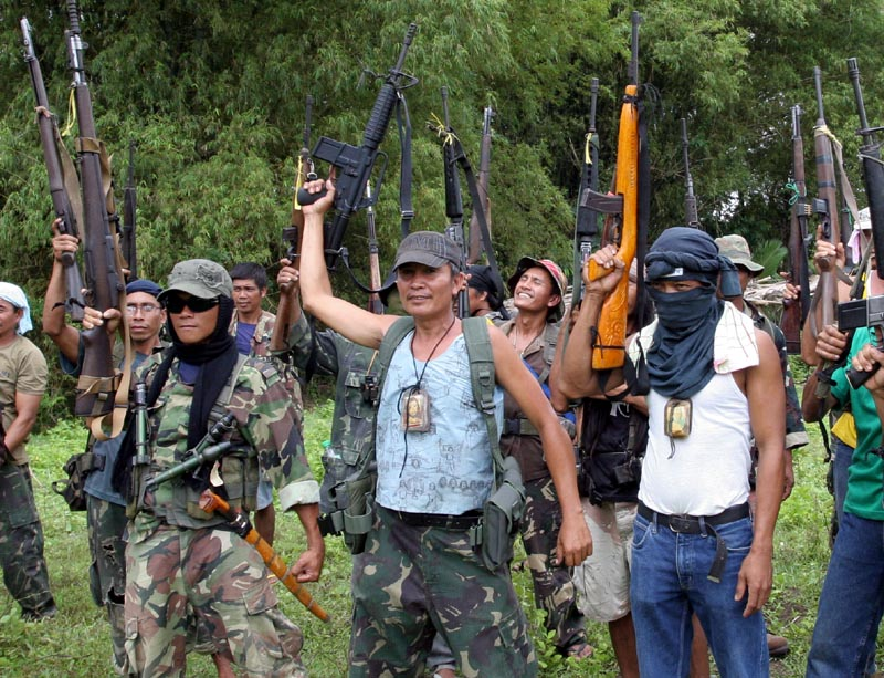 Members of a Christian paramilitary group raise their arms in the southern Philippines. The proliferation of unlicensed firearms is complicating the decades-old Muslim insurgency there