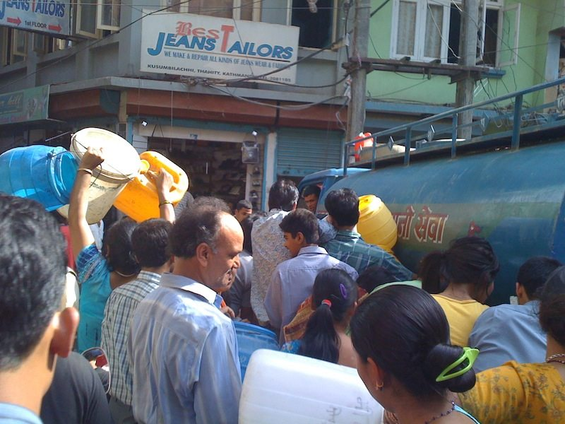 Desperate Kathmandu residents queue to collect water from a government water tanker