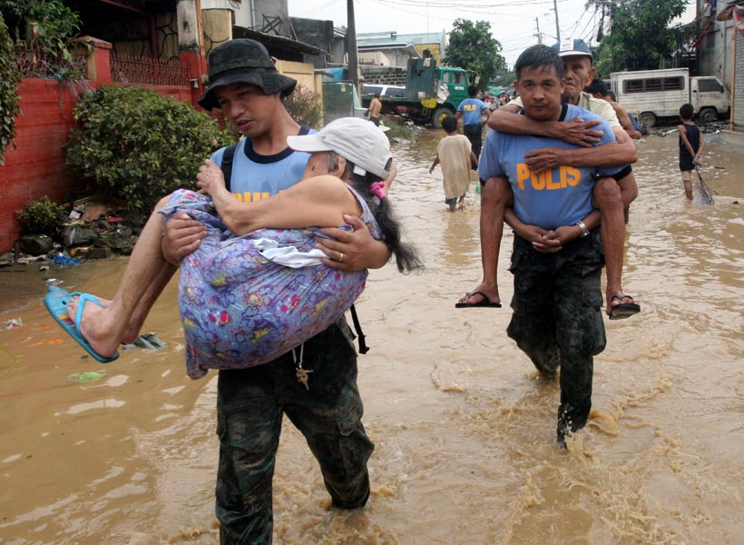 Manila - Police evacuate an elderly couple from a flooded section of suburban Pasig city east of Manila on 28 September 2009