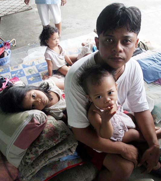 Cainta, Philippines - Ryan Leyva, 25, ponders the future with his children at an evacuation camp in the Philippines. Levya says life at the crowded evacuation centre has been hard, but he was lucky to survive Manila's epic flooding