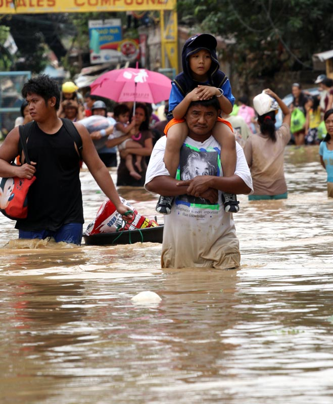 Manila - A father carries his daughter on his back as they wade through putrid, brown flood water in suburban Pasig district in Manila. At least 246 people were killed by tropical storm Ketsana on 26 September