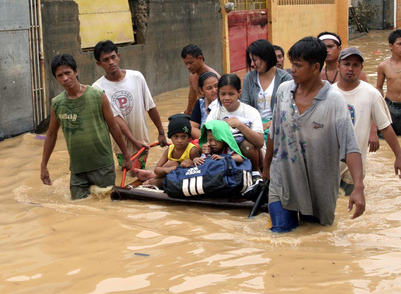 Residents use a makeshift raft to relocate children in this flooded section of Manila. Two weeks after unprecedented flooding in Manila and surrounding areas, the country has again plunged into crisis after continued rains by tropical storm Parma caused f
