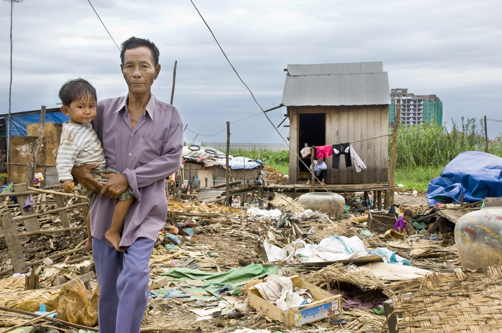 A man holds his child as he walks through the remains of a community known as Group 78 in central Phnom Penh on 16 July, 2009, a day before their forced eviction. Residents claimed they have been at location since 1983, giving them land rights, but govern