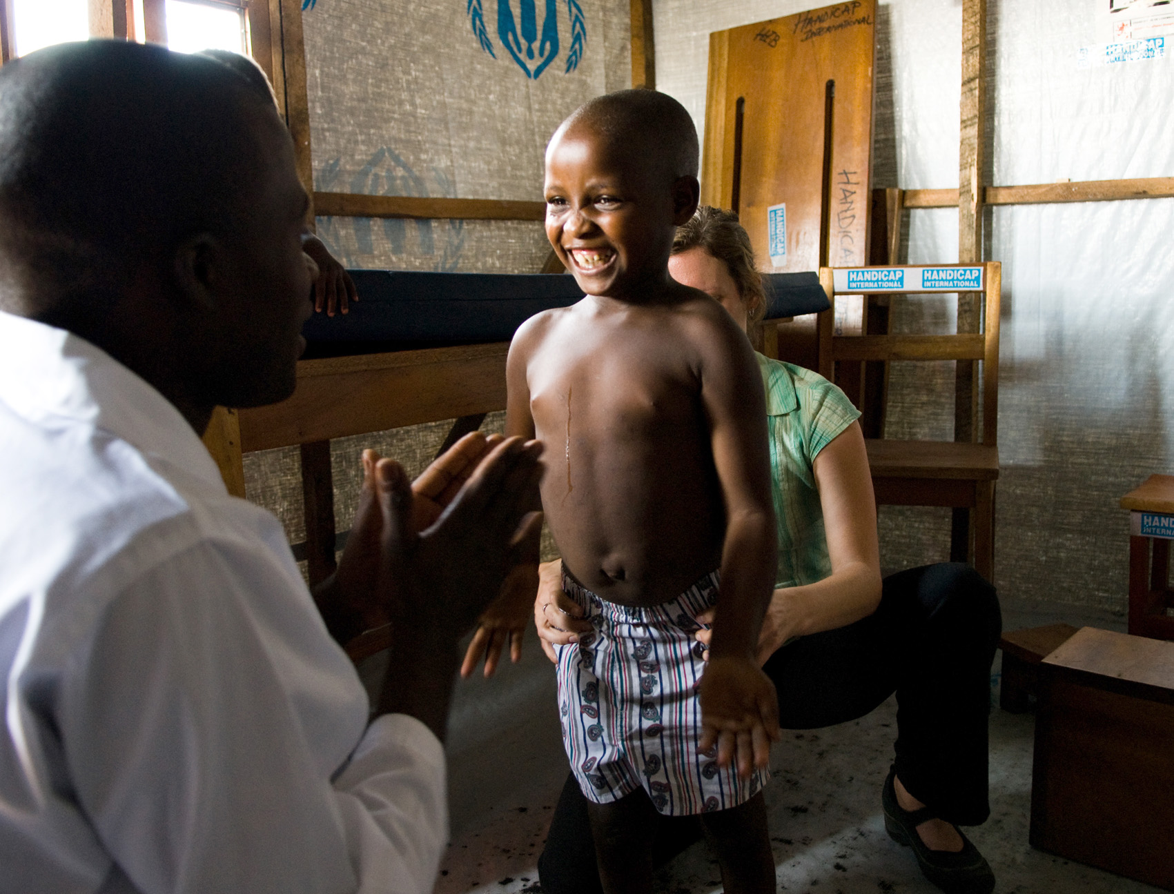 Helena, age 9, reacts joyfully to her therapist, Innocent, while being helped to maintain her balance by Laura Keyser at the Hanicap International IDP field clinic near Goma, DRC. Helena suffers from cerebral palsey and until recently was unable to contro
