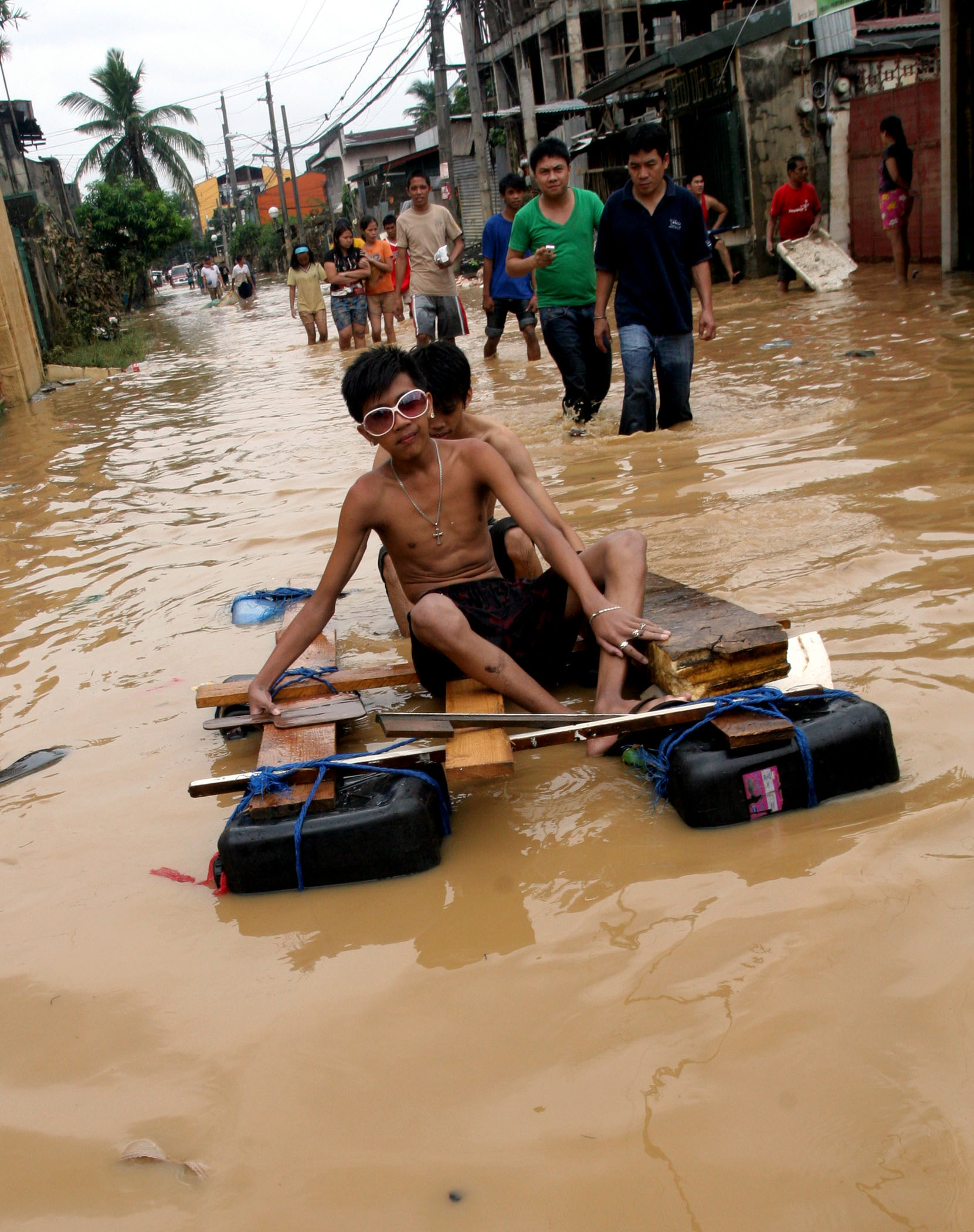 Manila - Filipino teen-aged boys play on stagnant flood waters that still submerge large areas in Manila, a month after tropical storm Ketsana dumped heavy rains. Government is now struggling to cotain an outbreak of leptospirosis, a deadly flood-borne ba
